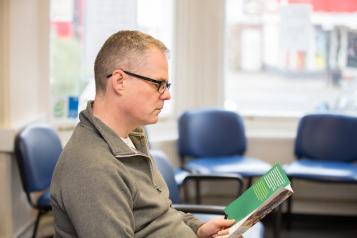 Man reading pamphlet