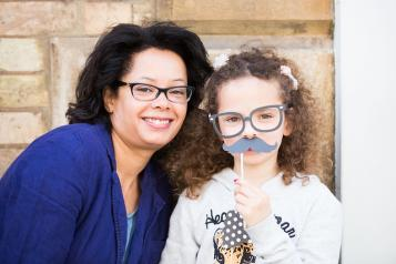 Woman and girl with paper moustache