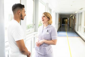 Young man chats with nurse about his health care